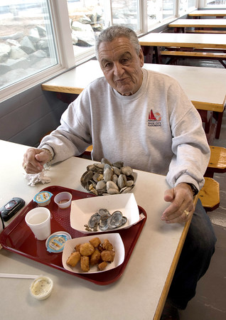 JIM VAIKNORAS/Staff  Joe Spero, of Haverhill enjoys scallops and steamers at Brown's Lobster Pound in Seabrook Friday. The popular eatery had a soft opening after it was damaged in a fire last summer.