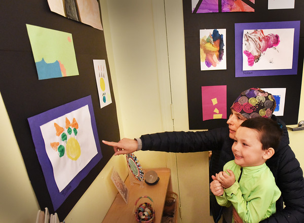 BRYAN EATON/Staff photo. Tristan Porter, 5, beams as his mom, Alana, asks about a piece of his artwork at the Newburyport Montessori School on Wednesday. Younger students completed six pieces of different subjects and styles and held the open house for their parents to view their efforts.