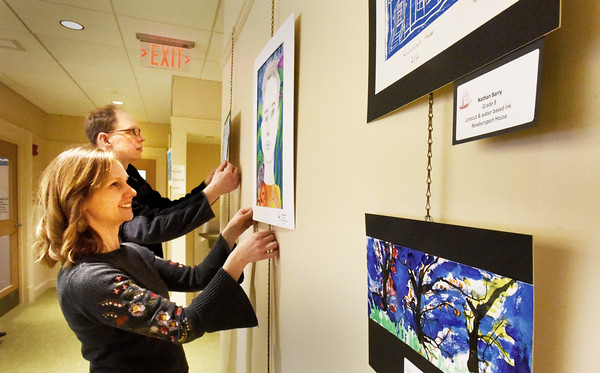 BRYAN EATON/Staff photo. Upper Molin Elementary and Nock Middle School art teachers Alyssa Gallegos, left, and Ben Ober arrange student art for a show at the Newburyport Senior Center, the first such collaboration between the school district and Council on Aging. Each of the district's art teachers selected seven works of art from their respective schools to put on display until May 25. The other teachers were Pam Standley Jamison from the Bresnahan School and Andrew Smith and Aileen Maconi from the high school.