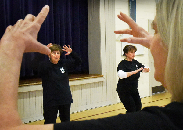 BRYAN EATON/Staff photo. Barbara Tindall leads Jean Abel and Alllyson Lawless, along with the rest of her Tai Chi class at the Brown School, in warmup excercise.