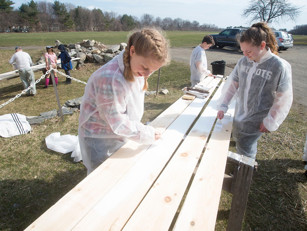 JIM VAIKNORAS/Staff photo Mackenzie Tanger, 11, Abby Doyle, 12, and Evan Laqueux, 10, prime some boards at the Spencer_Pierce Little Farm in Newbury Friday morning. The girls were part of a group of about 50 students from grades 4, 5, and 6 from the River Valley Charter School in Newburyport who came out to the farm on Community Service Day.