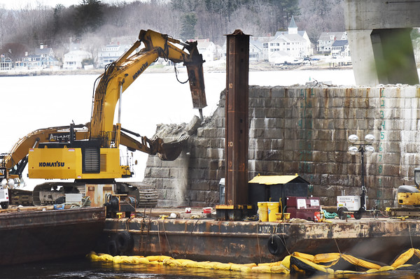 BRYAN EATON/Staff photo. An excavator catches stone being chiseled away from one of the bridge piers being demolished from the old Whittier Bridge on Tuesday. Work on the pedestrian and bicycle path above on the northbound lane of the new bridge is well underway.
