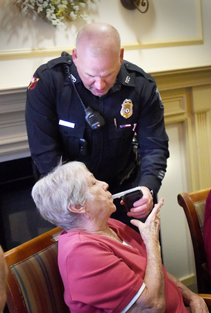 BRYAN EATON/Staff photo. Newburyport police officer Michael Wilichoski administers a breathalyzer test to Atria Merrimack Place resident Ruth Miller during the facility's happy hour in their pub. They were holding an informational session for National Alcohol Screening Day showing how Alcohol affects people differently as we age.