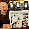 BRYAN EATON/Staff photo. Eric Small, head of the Seabrook historical society, is in the process of publishing about a 200 page book with 450 photos of Seabrook throughout the years, ranging from the town's establishment in 1636 to the 1950's and 1960's. This is a part of the town's 250th anniversary celebration in August. He's hoping to sell books to help contribute to the celebration.