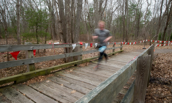JIM VAIKNORAS/Staff photo A runner crosses a wooden bridge during the Tortoise and Hare 10K at the Rail Trail in Salisbury Saturday.