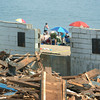 Salisbury: Beachgoers and paddle boarders take in the sun beyond the ruins of the Sidewalk Cafe at Salisbury Beach which came down on Tuesday. Bryan Eaton/Staff Photo