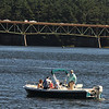Amesbury: A group of boater relax on the Merrimack River as traffic builds on the Whittier Bridge. Jim Vaiknoras/staff photo