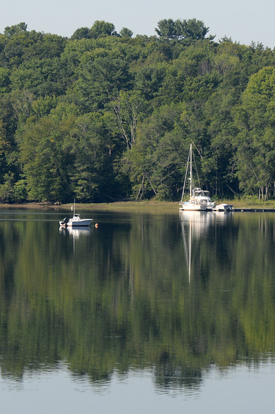 BRYAN EATON/ Staff Photo. A calm Merrimack River reflects this sailboat docked along River Road in Merrimac on Tuesday morning.