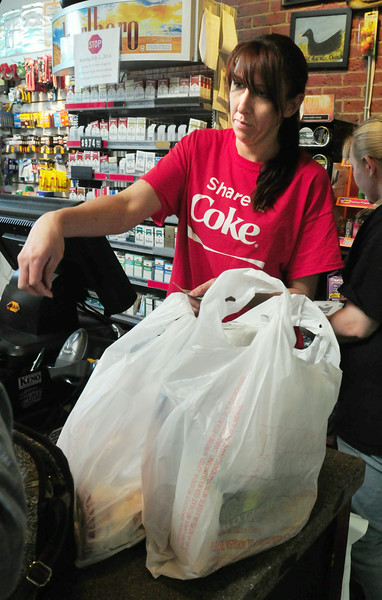 BRYAN EATON/ Staff Photo. Katie Munroe of the Black Duck Market and Deli gives change to a customer, their purchases in plastic bags. The Newburyport city council has passed an ordinance banning such bags that are of a thin material with handles.
