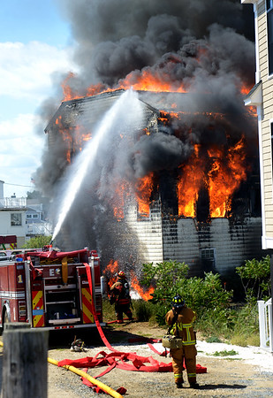 JIM VAIKNORAS/Staff photo Firefighters battle a blaze on Plum Island Saturday afternoon.