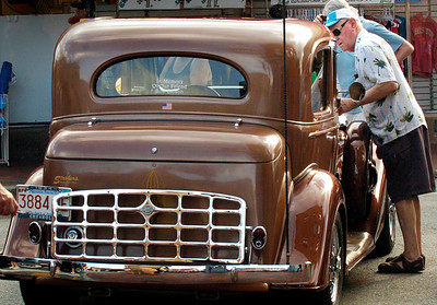 BRYAN EATON/Staff photo. Gordon Carmichael of Woburn checks out a 1934 Chevy Master Town Sedan on Pleasant Street at the Newburyport Car Show.