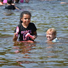 BRYAN EATON/Staff photo. Chloe Volens, 3, of Amesbury laughs with her newly made friend Mia Beth Brown, 5, also of Amesbury. The two were cooling off at Amesbury's Lake Gardner Beach.