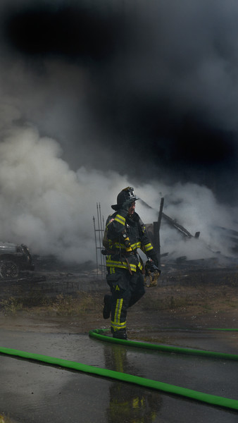 JIM VAIKNORAS/Staff photo  A firefighter removes his mask as he takes a break while battling a blaze on on Plum Island Saturday afternoon.