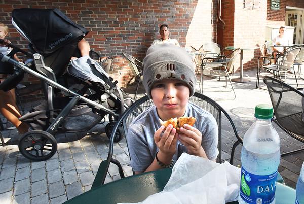 BRYAN EATON/Staff photo. Cal Eaton, 8, of Newburyport enjoys his bagel in the patio area.