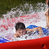 BRYAN EATON/Staff photo. Bryan Santos, 8, of Salisbury sprays up a wave as he moves in the water slide at the Boys and Girls Club in Salisbury. They were having a end of the summer carnival with food, games and other activities.