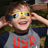 BRYAN EATON/Staff photo. Conri Belanger, 5, of West Newbury checks out the solar eclipse in the back yard of the G.A.R. Memorial Library in West Newbury which had pairs of special viewing glasses for people to share.