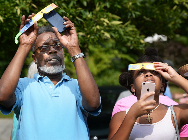BRYAN EATON/Staff photo. David French of Beverly, and his daughter, Simone, 16, try to take photos of the eclipse through their cellphones.
