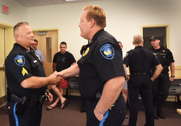 BRYAN EATON/Staff photo. Salisbury police Sgt. Chuck Scione is congratulated by chief Thomas Fowler on his last day of duty. Town officials and fellow officers joined in the small sendoff with a cake.