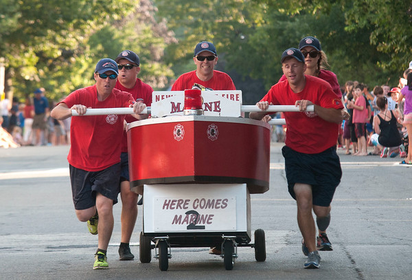 JIM VAIKNORAS/Staff photo The Newburyport Fire Department sprint to the finish in the Lions Club Bed Race on Federal Street in Newburyport Thursday night.