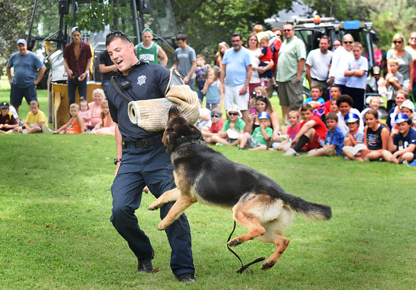 BRYAN EATON/Staff photo. Sgt. Chris Auger, pictured, and Capt. Tom Cote of the Essex County Sheriff's Department's K-9 unit gives a demonstration with Dash at Yankee Homecoming's Kids Day in the Park.