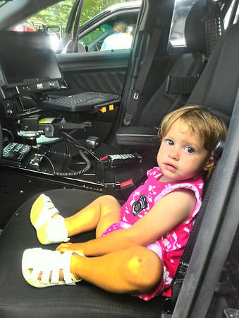 JIM SULLIVAN/Staff photo. Riley Brown, 18 months, of Salisbury sits in Newburyport Police Department Cruiser 504 at the Yankee Homecoming Kids Day in the Park.