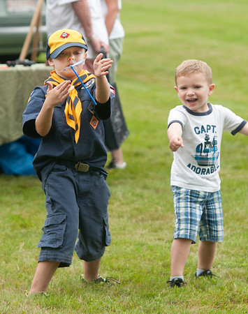 JIM VAIKNORAS/Staff photo Pack 21 Cub Scout Nate Brown helps James Grayson, 3, of Amesbury fly a stick copter during Family Day at Maudslay Saturday morning.