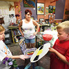 BRYAN EATON/Staff photo. Renee Schneider of Colorful Kids works with Amelia Hopp, 6, and A.J. Scrupps, both 6, work on props for a play they're putting on.