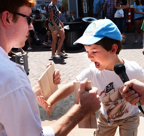 BRYAN EATON/Staff photo. Adrien Messlaar, 6, of Ipswich breaks a board held by Henry Brewster, teacher of the Dojo Dem Team from Tokyo Joe's which gave a demonstration in Market Square. He was visiting his grandparents Dirk and Deb Messlaar on Plum Island.