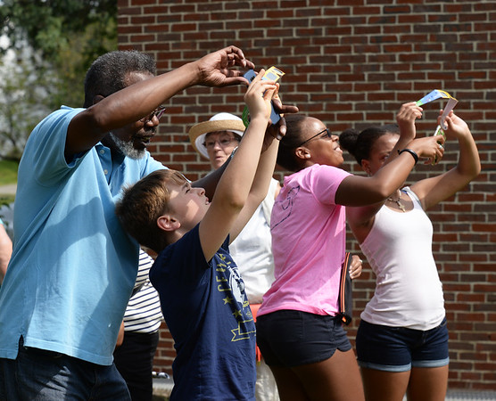 BRYAN EATON/Staff photo. Checking out the eclipse at the G.A.R. Memorial Library in West Newbury trying to take photos with cellphones looking through special glasses.