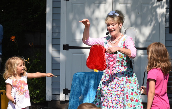 BRYAN EATON/Staff photo. Newburyport's Debbie O'Carroll got children into her magic act, here changing a flag of a toad into a prince. She was performing at the Emma Andrews Library and Community Center in Newburyport's south end.