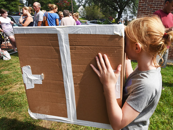 BRYAN EATON/Staff photo. Kaleigh Belanger, 8, of West Newbury looks at the eclipse through a box with a pinhole made by Jenna Sigman of Danvers.