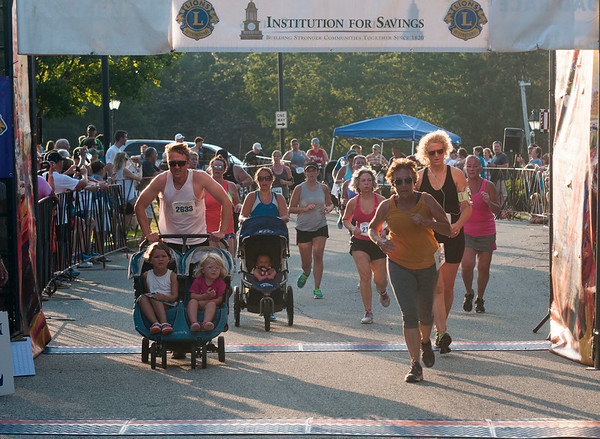 JIM VAIKNORAS/Staff photo  Runners cross the finish line at the Newburyport Lions Club 5k Tuesday night.
