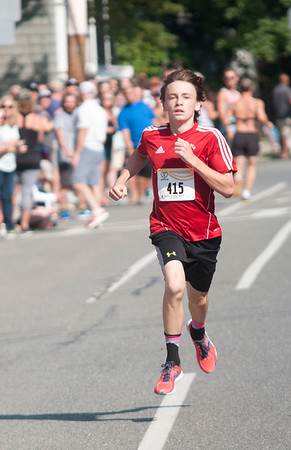 JIM VAIKNORAS/Staff photo High Street Mile Kid's race winner Will Coogan sprints to the finish Sunday morning in front of Newburyport High School.