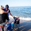 JIM VAIKNORAS/Staff photo Ron Dienstmann  Hugs his wife Dawn Brandmark on Plum Island as he completes a cross country bike trip having left Portland Oregon on June 24th.