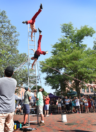 "BRYAN EATON/Staff photo. David Graham, top, and Tobin Renwick of the ""Red Trouser Show"" perform their act in Market Square with members of the audience holding the ladder up with ropes."
