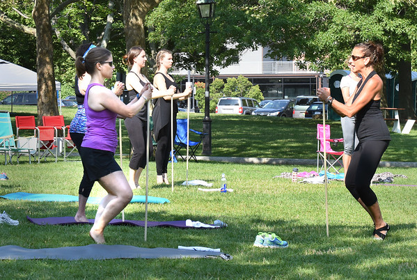 BRYAN EATON/Staff photo. Participants in the Yankee Homecoming Waterfront Exercise Series use batons in one unit of their workout.