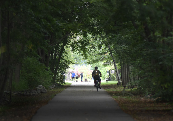 BRYAN EATON/Staff photo. A bicyclist heads down the Clipper City Rail Trail which looks like railroad tunnel with the canopy of trees and lack of sunlight. The sunshine is schuduled to return later in the day today and then Friday and into Saturday.