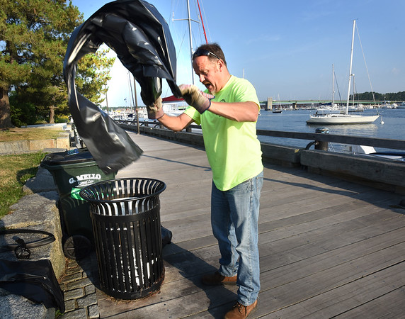 BRYAN EATON/Staff photo. Newburyport DPW employee Gary Westphal replaces garbage liners on the Boardwalkk. With the crowds that Yankee Homecoming, his department stays busy.