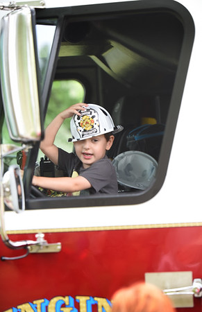 BRYAN EATON/Staff photo. Theo Rossi, 4, of Byfield sits ina Newburyport Fire Department engine at Yankee Homecoming's Kids Day in the Park.