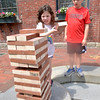 JIM VAIKNORAS/Staff photo Emma Greenberg, 5, places a piece during a game of Giant Jenga in Market Square in Amesbury against her brother Zach, 8, this past weekend.