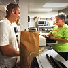 BRYAN EATON/Staff photo. Linda Garcia rings up Travis Sumner's order of a dozen bagels, mostly sesame, which he insisted on paying for though Garcia wanted to give him as he was the first customer. He won the Newburyport Education Foundation auction and had the honor of being the first customer of the reopened Abraham's Bagels.