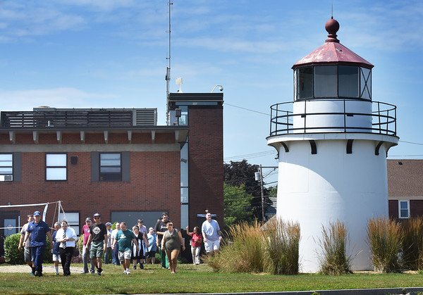 BRYAN EATON/Staff photo. People pass the Range Light as they exit the coast guard station after a tour of the interior.