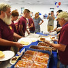 BRYAN EATON/Staff photo. Volunteers put together plates of pulled pork sandwiches and cole slaw for the Veteran's Luncheon.
