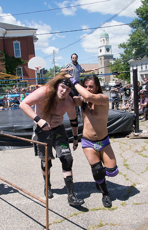 JIM VAIKNORAS/Staff photo Vern Vicallo deals out some punishment to Tim Lenox during the Atlantic Pro-Wrestling match at Old Fashioned Sunday on Mall in Newburyport Sunday.