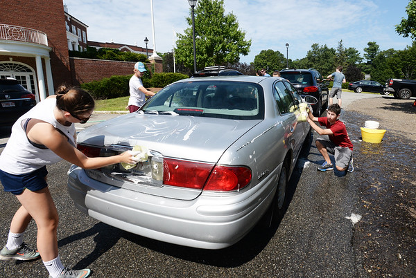 BRYAN EATON/Staff photo. Members of the Newburyport High School junior class held a car wash and bake sale at the school on Thursday. They were raising money to defray the costs of buses for their prom in the spring.