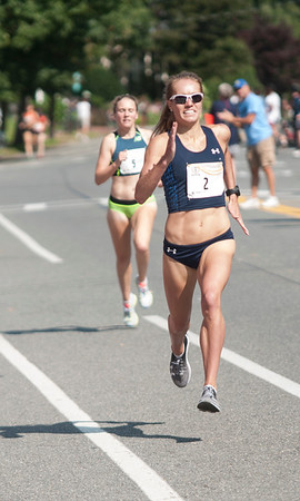 JIM VAIKNORAS/Staff photo High Street Mile Woman's race winner Rachel Scheider edges out 2nd place finisher Katrina Coogan Sunday morning in front of Newburyport High School.