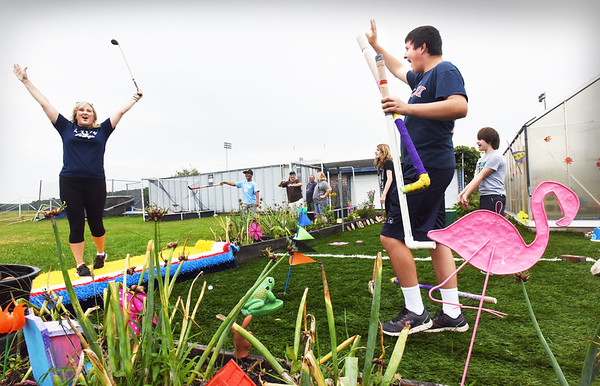 BRYAN EATON/Staff photo. Brett Johnson, 20, right, cheers with his mother, teacher's aide Tracy Johnson as she teed off on the new miniature golf course special education students built at Triton High School.