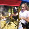 BRYAN EATON/Staff photo. Lexi Locke, 15, of Amesbury hands out popcorn at the Boys and Girls Club carnival on Thursday afternoon. She was volunteering, part of the 75 hours of volunteer work for Amesbury High School students that they need to graduate.