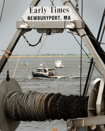 BRYAN EATON/Staff photo. A pleasure boat motors up the Merrimack River in Newburyport framed by the gear of the fishing boat Early Times on Tuesday afternoon. After some rain overnight, the weather is looking sunny, dry and warm for the weekend.