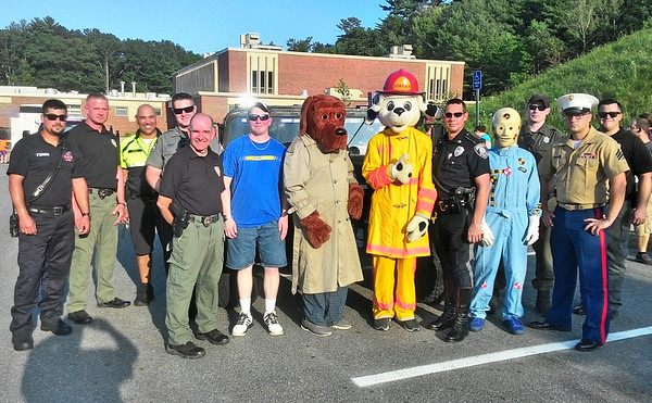 JIM SULLIVAN/Staff photo. Various participants pose in front of Salisbury Police Department's Humvee at the National Night Out at Amesbury High School Tuesday night.